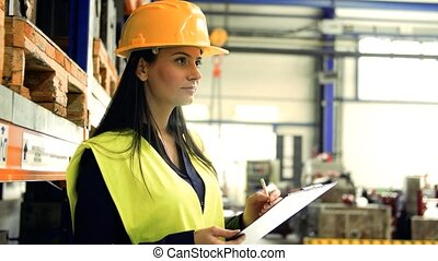 An industrial woman engineer in a factory checking documents.