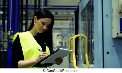 An industrial woman engineer in a factory checking...