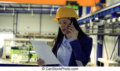 An industrial woman engineer in a factory with smartphone making a phone call.