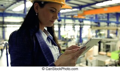 An industrial woman engineer in a factory with tablet, working.