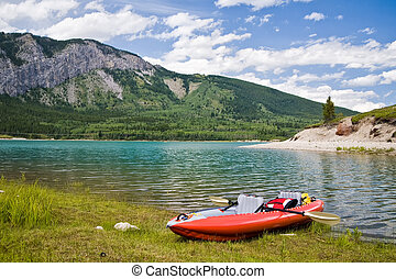 An inflatable kayak on a lake in the mountains