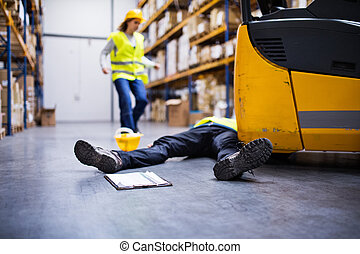 An injured worker after an accident in a warehouse. - An...