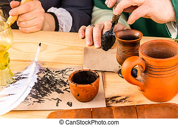 an inkwell with a white quill pen traditional handwritten accessories stand on a wooden table