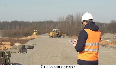 An inspector in a signal vest and a white helmet with black glasses makes notes in his folder on the quality of the road curb and road construction, copy space