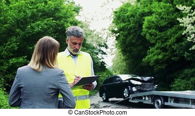An insurance agent talking to a woman outside on the road...