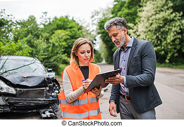 An insurance agent talking to a woman outside on the road after a car accident.