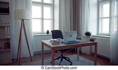 An interior of home office with desk and laptop. Slow...