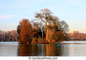 An island covered in trees on Lake Annecy in autumn, France.