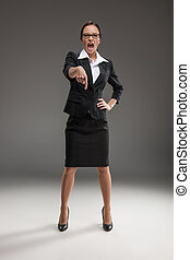 An isolated portrait of angry business woman. boss screaming and pointing her finger on grey background