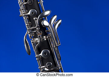 An oboe up close isolated against a blue background in the horizontal format with copy space.