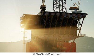 An offshore oil platform at sunset light