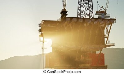An offshore oil platform at sunset light