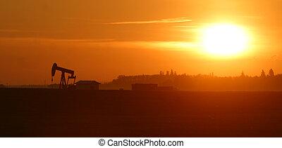 an oil pump jack at sunrise