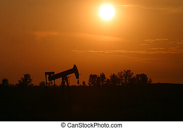 An oil pump jack is silhouetted by the setting sun in rural Alberta, Canada.