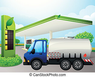 An oil tanker in front of a gasoline station