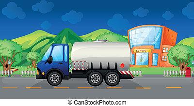 An oil truck passing a school