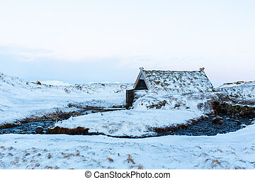 An old bathhouse with a hot spring in the mountains of Iceland. Iceland winter landscape