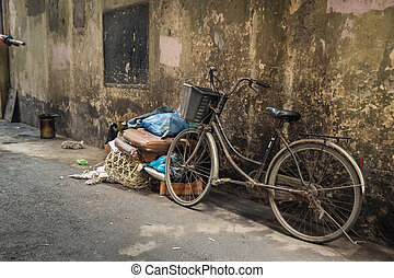 An old bike in a dirty alley