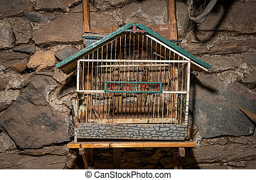 An old birdcage hanging in front of a stone wall - Closeup ...