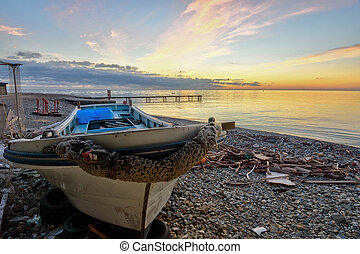 An old boat on the beach against the backdrop of a beautiful sea sunset