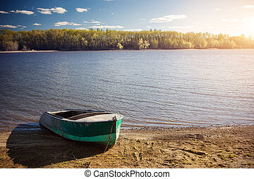 An old boat on the shore of the pond