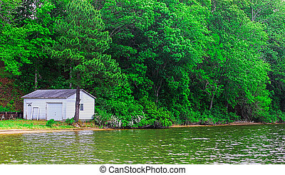 An old boathouse along the river shore up against the woods on a summer day