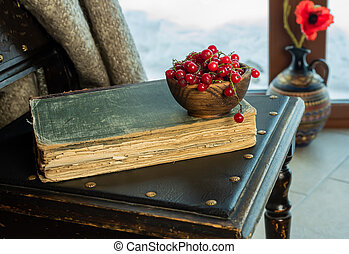 An old book lies on an old chair by the window
