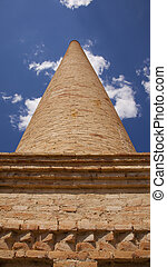 an old brick chimney against the blue sky