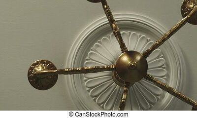 An old bronze chandelier on the ceiling of a dolly shot