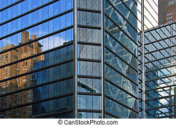 An old building can be seen on the shiny facade of a modern skycraper