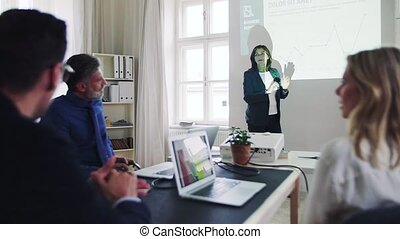 An old businesswoman giving a presentation to colleagues in a modern office.