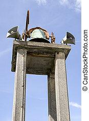an old church bell against a blue sky