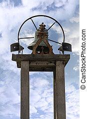 an old church bell against a cloudy sky