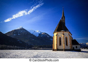An old church on the top of the mountain in italian alps during winter season