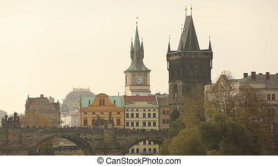 An old clock tower near the bridge in Prague, a bridge across the river in the old town
