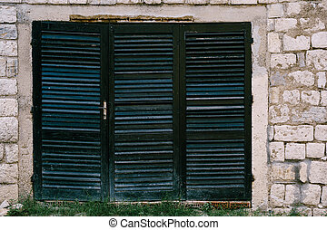 An old closed window in black with a blue tint with blinds on a brick wall.