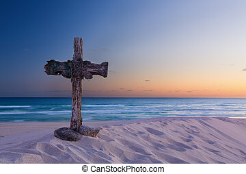 An old cross on sand dune next to the ocean with a calm...