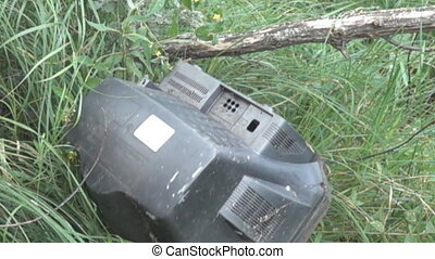 An old dirty telly falls off branch in woods. Decline television in traditional style concept. The laws of market and technological revolutions, new technologies. Super slow motion 1000 fps