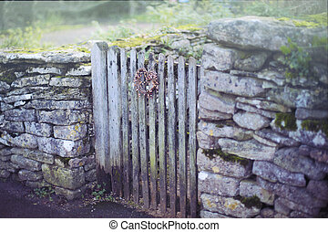 An old English dry stone wall with a nostalgic christmas dried twig wreath hanging on wooden gate.