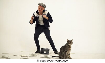 An old fashioned man in a tweed cap with a phone in his hands dancing with money on the floor and a cat in the foreground