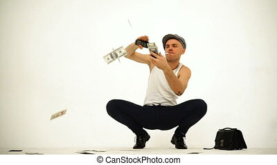 An old fashioned squatting slav in a tank top tweed cap stitting with a leather purse throwing money rain on white background