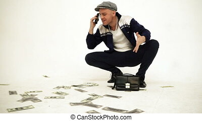 An old fashioned squatting slav in a tweed cap with a leather purse talking angrily on phone with money on the floor
