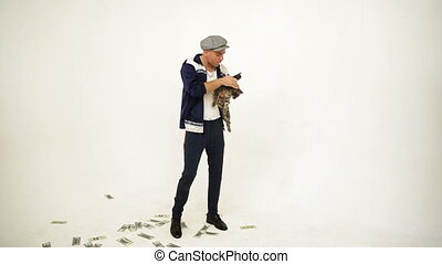 An old fashioned standing slav in a tweed cap holding and petting a cat in his hands, walking and talking angrily on phone with money on the floor
