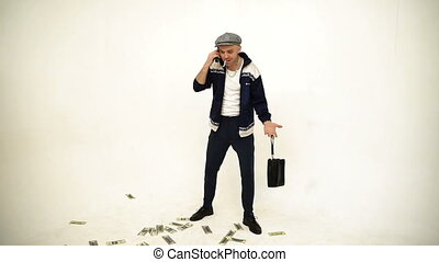 An old fashioned standing man in a tweed cap with a leather purse walking and talking angrily on phone with money on the floor