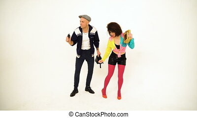 An old fashioned young man and a girl dancing. Girl is holding a boombox, man has got a purse and a phone in his hands