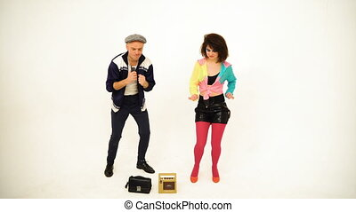 An old fashioned young man and a girl dancing. Man is holding a phone; purse and boombox are on the floor