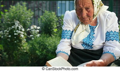 An old grandmother is sitting on the street and reading a book. She is dressed in national ukrainian clothing vyshyvanka