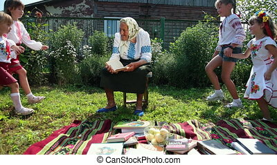 An old grandmother is sitting on the street and reading a book. She is dressed in national ukrainian clothing vyshyvanka. The girls run up and hug their grandmother