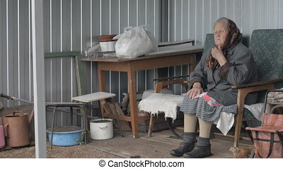 An old grandmother sitting in a chair on the street. A woman...