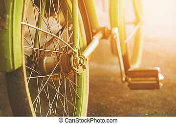 An old green Bicycle stands on the asphalt in the summer, illuminated by the rays of the warm bright sun.